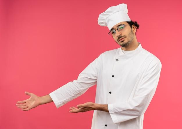 Giovane cuoco maschio indossa divisa da chef e punti di occhiali con la mano a lato