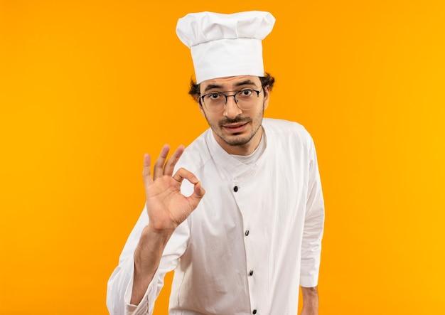 Giovane cuoco maschio che indossa l'uniforme dello chef e bicchieri che mostrano il gesto okey
