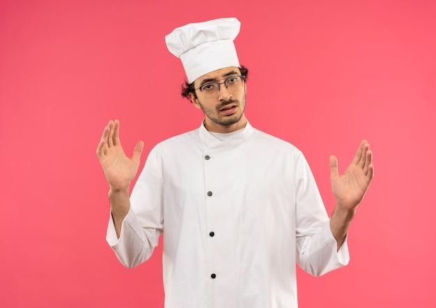 Giovane cuoco maschio che indossa l'uniforme dello chef e bicchieri che mostrano le dimensioni