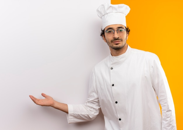 Young male cook wearing chef uniform and glasses showing with hand white wall