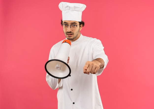Young male cook wearing chef uniform and glasses speaks on loudspeaker and showing you gesture