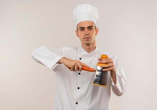 Молодой мужчина-повар в униформе шеф-повара натертая морковь на изолированной белой стене