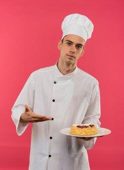 孤立したピンクの壁のプレートにハンドケーキを持ってシェフの制服を持ってポイントを身に着けている若い男性料理人
