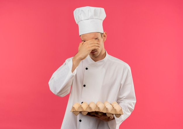 Young male cook wearing chef uniform holding batch of eggs covered eyes with hand