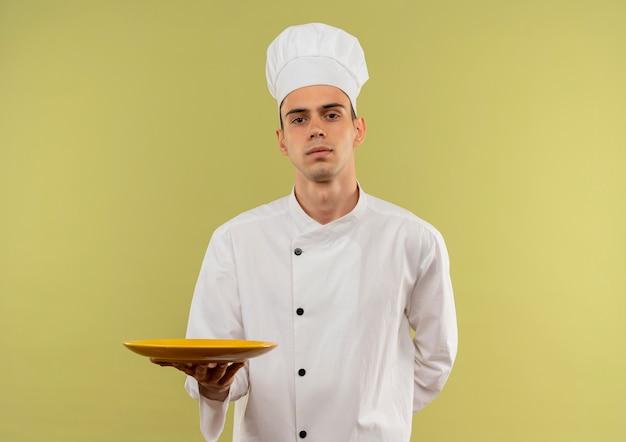 복사 공간이 격리 된 녹색 벽에 접시를 들고 요리사 유니폼을 입고 젊은 남성 요리사