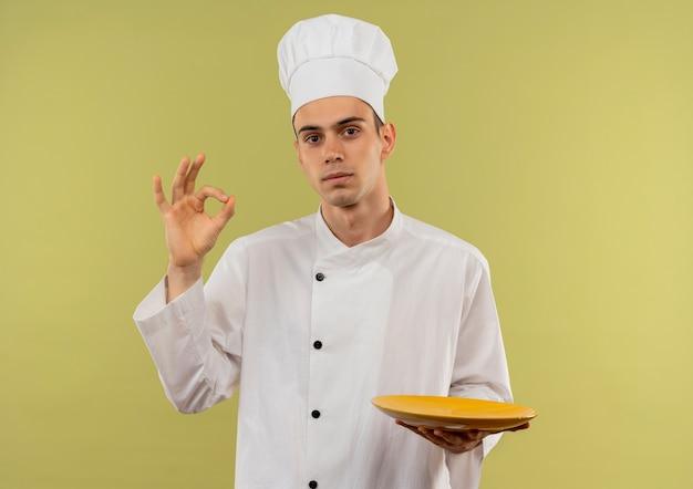 Молодой мужчина-повар в униформе шеф-повара держит тарелку, показывая жест ок на изолированной зеленой стене с копией пространства