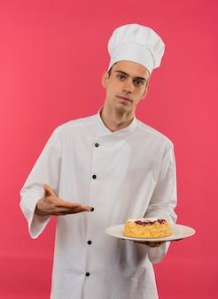 Giovane cuoco maschio che indossa la tenuta uniforme dello chef e punti con la torta di mano sul piatto sul muro rosa isolato