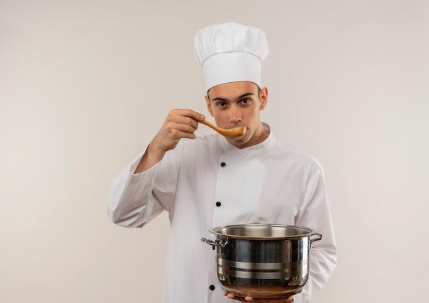 孤立した白い壁にスプーンからスープを試して鍋を保持しているシェフの制服を着た若い男性料理人