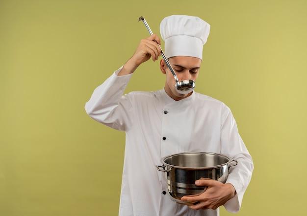 コピースペースでスープを試して鍋を保持しているシェフの制服を着た若い男性料理人