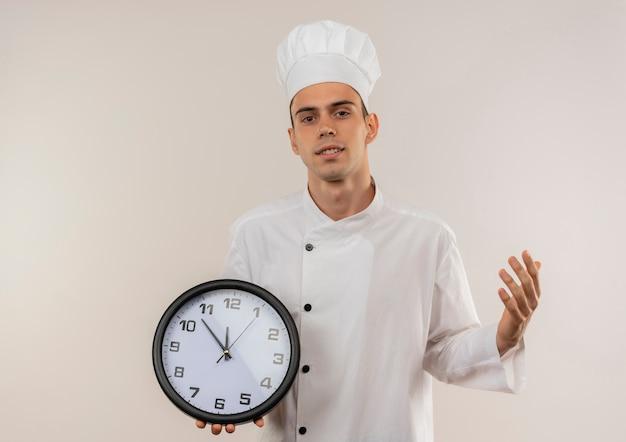 コピースペースと隔離された白い壁に壁時計を保持しているシェフの制服を着た若い男性料理人