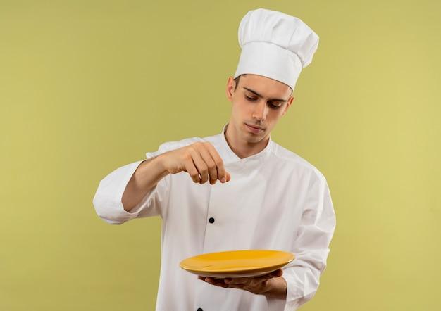 Il giovane cuoco maschio che indossa l'uniforme del cuoco unico che osserva il piatto fa finta di versare il sale con lo spazio della copia