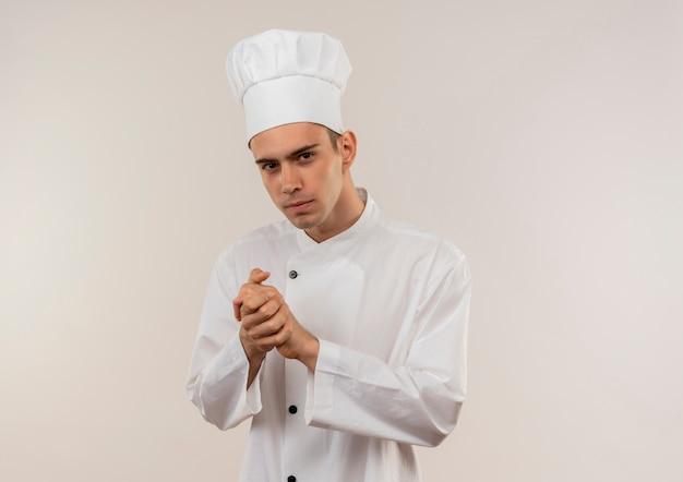 복사 공간이 격리 된 흰 벽에 악수 제스처를 보여주는 요리사 유니폼을 입고 젊은 남성 요리사