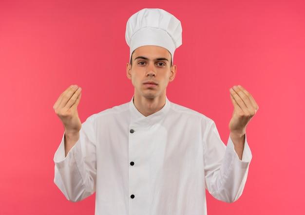 격리 된 분홍색 벽에 팁 제스처를 보여주는 요리사 유니폼을 입고 젊은 남성 요리사