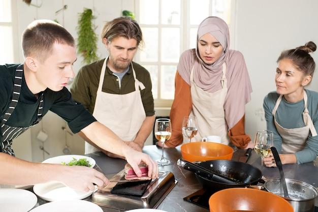 マスタークラスの間に彼の学習者の間で大きな台所のテーブルの上に曲がり、燻製牛肉の断片を切るエプロンの若い男性の料理のコーチ