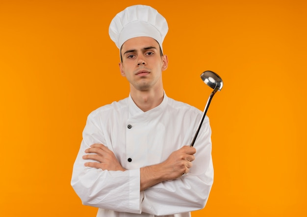 Young male cool wearing chef uniform crossing hands holding ladle on isolated yellow wall