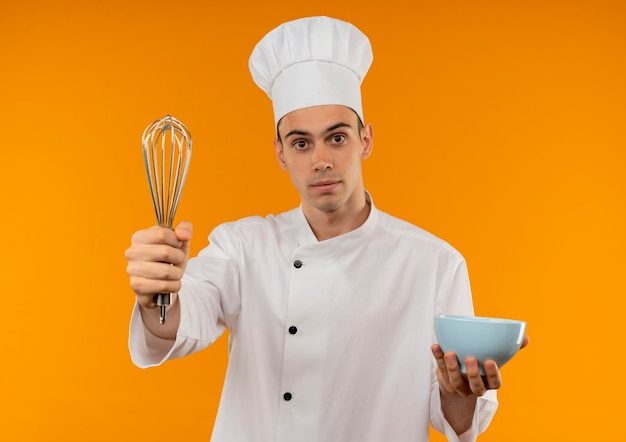 Young male cool wearing chef uniform holding bowl and holding out whisk on isolated yellow wall