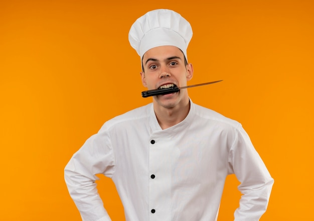 Young male cool wearing chef uniform holding knife in mouth on isolated yellow wall