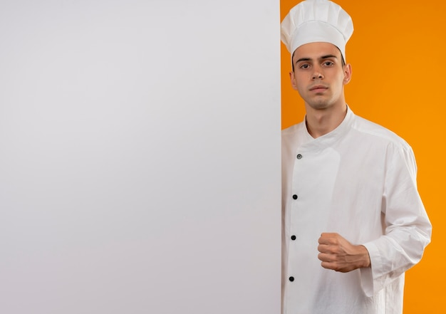 Young male cool wearing chef uniform holding white wall showing strong gesture on isolated yellow wall with copy space