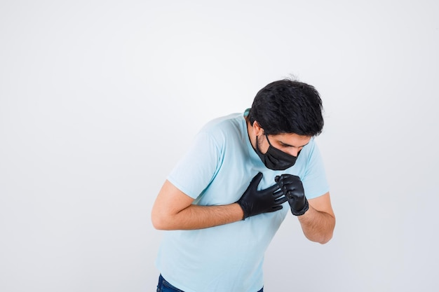 Giovane maschio che tossisce mentre sta in maglietta e sembra malato. vista frontale.
