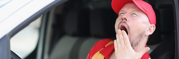 若い男性の宅配便の運転手は車を運転しながらあくびをします