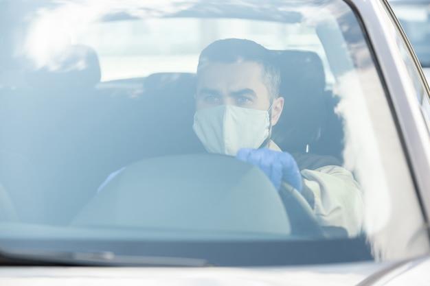 検疫中にクライアントの家にオンラインショップの注文を配信しながら車を運転する保護マスクと手袋の若い男性の宅配便