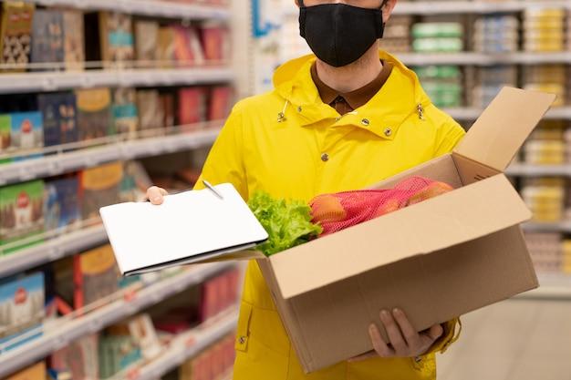 Молодой мужчина-курьер в форме и защитной маске держит открытую картонную коробку со свежими продуктами и документом со списком товаров