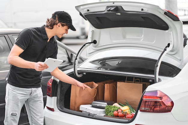 Young male courier looking for online order and put it in the trunk of a white car