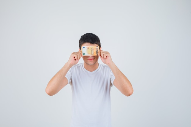 Young male covering eye with euro banknote in t-shirt and looking cheery. front view.