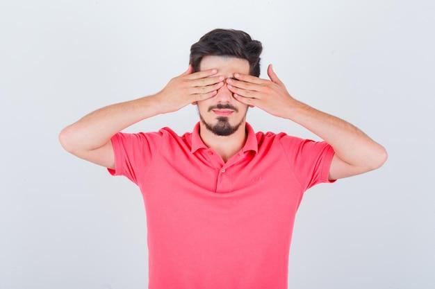 Tシャツを着て手で目を覆い、かわいく見える若い男性。正面図。