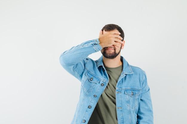 Tシャツのジャケットで手で目を覆って興奮している若い男性