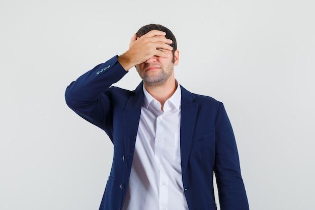 Giovane maschio che copre gli occhi con la mano in camicia e giacca e sembra imbarazzato