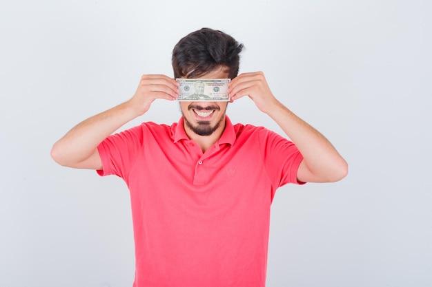 Молодой мужчина закрыл глаза деньгами в футболке и выглядел радостным. передний план.