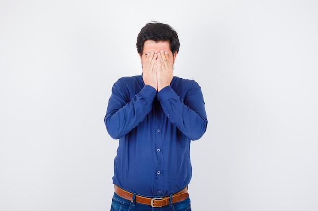 젊은 남성 셔츠, 청바지에 손으로 얼굴을 덮고 스트레스를 찾고. .