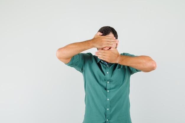 녹색 셔츠에 손으로 얼굴을 덮고 숨겨진 앞모습을 바라보는 젊은 남성.