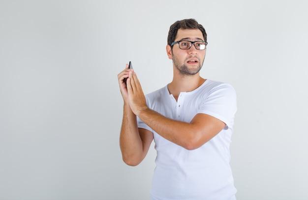 Молодой мужчина закрывает микрофон на смартфоне в белой футболке, очках и выглядит взволнованным