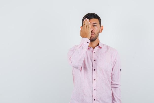 Giovane maschio che copre un occhio con la mano in camicia rosa, vista frontale.