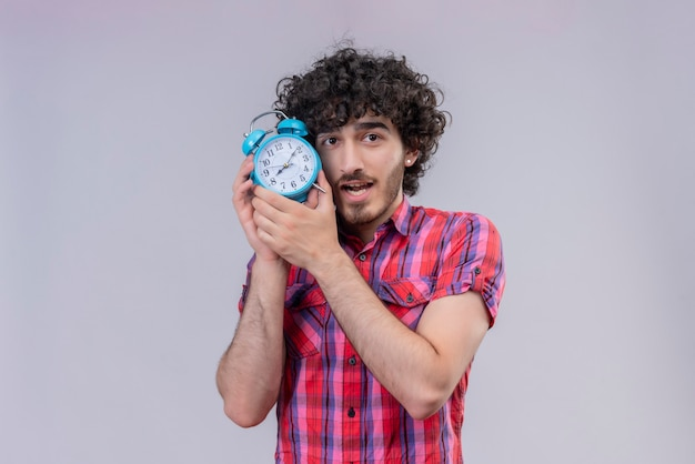 Young male curly hair isolated  colorful shirt alarm clock