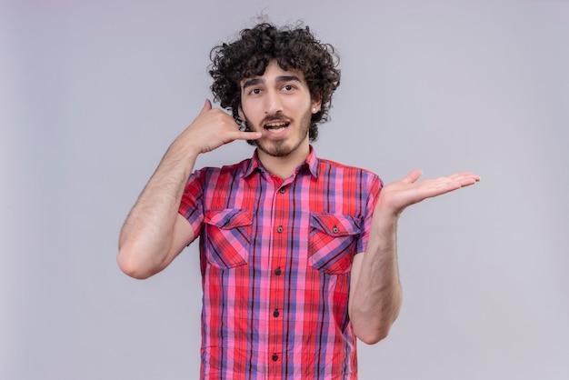 I giovani capelli ricci maschii hanno isolato il gesto variopinto di chiamata della camicia e l'elemento del segno della tenuta