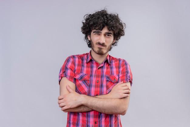 Giovane maschio capelli ricci isolato camicia colorata braccia incrociate sorrisetto