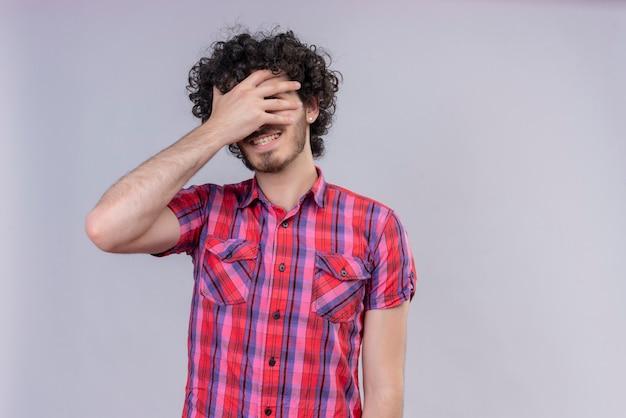 Giovane maschio capelli ricci isolato camicia colorata cosegna gli occhi