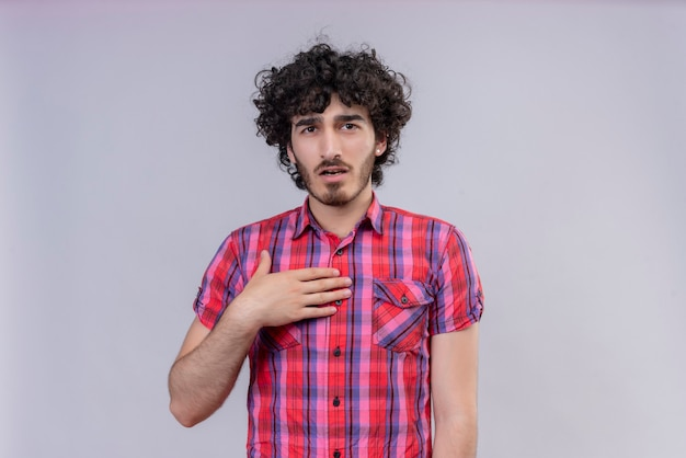 若い男性の巻き毛は、ショックを受けた胸にカラフルなシャツの手を分離しました