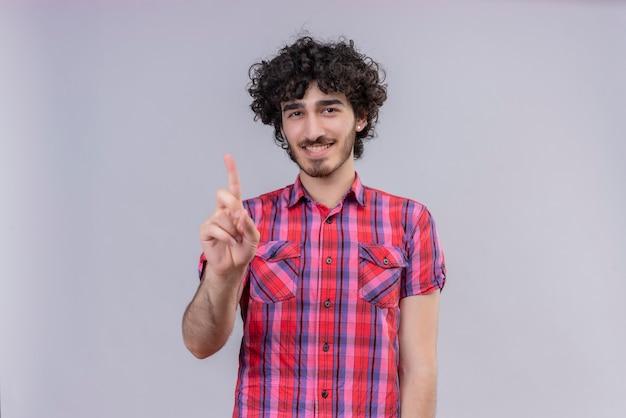 Молодой мужчина вьющимися волосами изолировал красочную рубашку одним пальцем