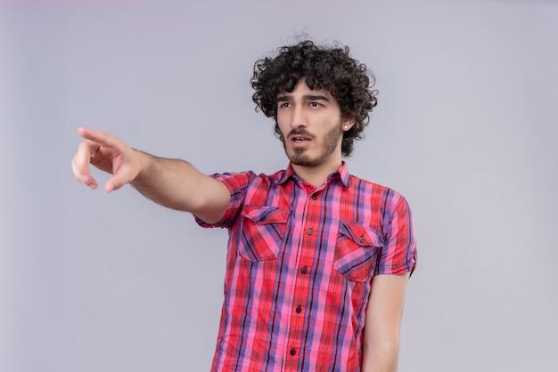 若い男性の巻き毛は遠くを指すカラフルなシャツを分離しました