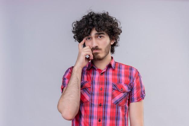 若い男性の巻き毛は、寺院を引っ掻くことを考えてカラフルなシャツを分離しました