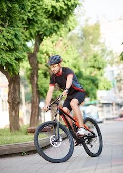 Молодой велосипедист мужского пола выполняет трюки на улицах города