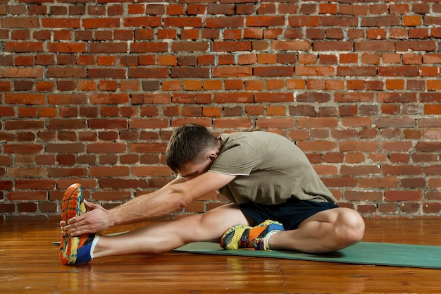 Young male cyclist athlete training and doing workout on gym mat