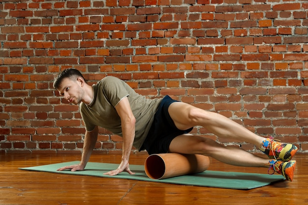 Young male cyclist athlete training and doing workout with barrel on gym mat