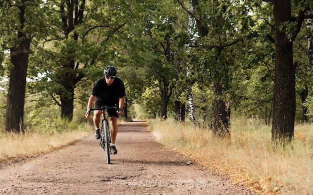 ヘルメットと眼鏡をかけた若い男性サイクリストが田舎道で自転車に乗る。砂利自転車の運動選手は、新鮮な空気のトレーニングを楽しんでいます。