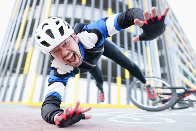 헬멧과 보호 장비를 착용 한 젊은 남성 사이클 선수가 자전거와 비행 초상화에서 떨어졌습니다.