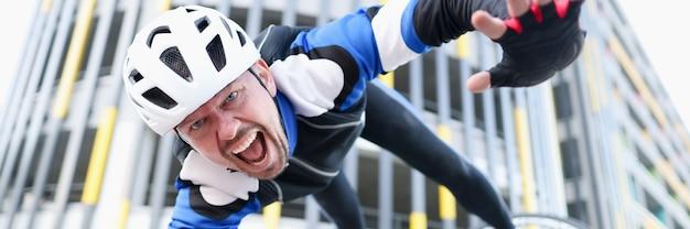 ヘルメットと保護具を身に着けている若い男性サイクリストが自転車と飛行の肖像画から落ちた
